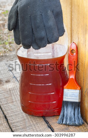 against the backdrop of the boards is a bottle of varnish and brush - stock photo