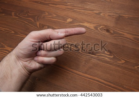 against the background of a wooden table top, gestures fingers - stock photo