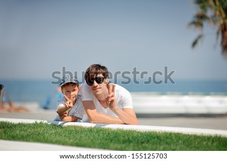 against the sea dad in sunglasses with a young son - stock photo
