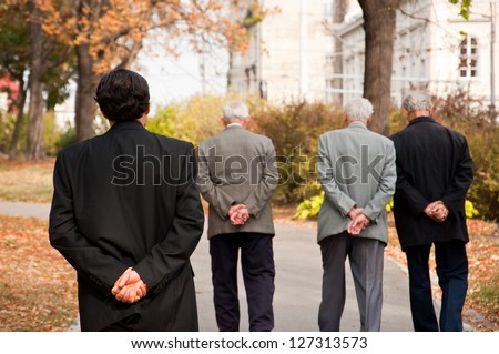 age difference, young man in the suit walking behind seniors,with both hands on his back,thinking about ,passing of life - stock photo