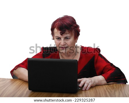 Age is no obstacle to learn modern technologies - senior woman in red dress sits behind table and seriously looks to laptop screen. Portrait isolated on white background - stock photo