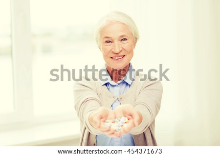 age, medicine, health care and people concept - happy senior woman with pills at home or hospital office - stock photo