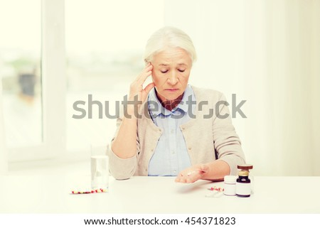 age, medicine, health care and people concept - senior woman with pills and glass of water at home - stock photo