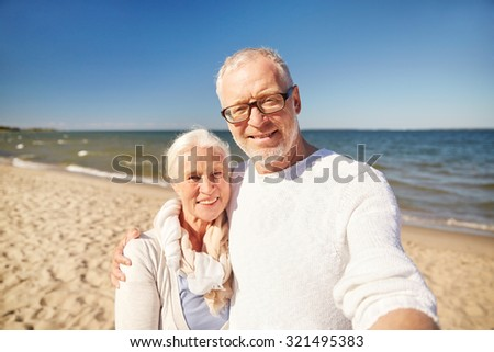 age, travel, tourism, technology and people concept - happy senior couple taking picture with smartphone selfie stick on summer beach - stock photo