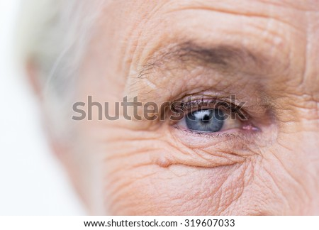 age, vision and old people concept - close up of senior woman face and eye - stock photo