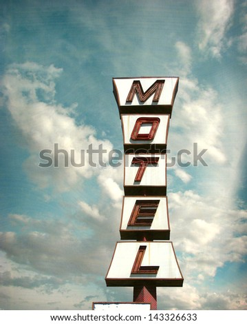 aged and worn vintage motel sign with dramatic sky - stock photo