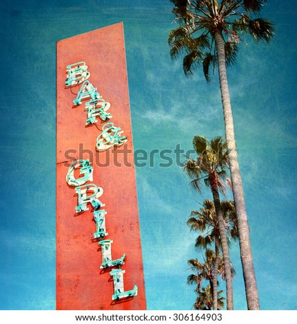 aged and worn vintage phoe of bar and grill sign with palm trees - stock photo