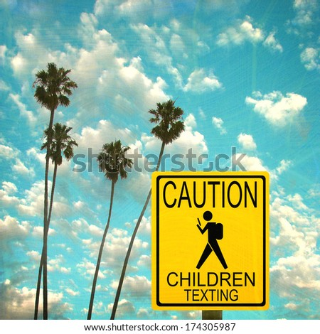 Aged and worn vintage photo of caution road sign with child texting - stock photo