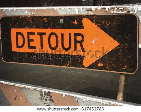 aged and worn vintage photo of detour sign with arrow - stock photo