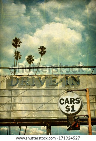 aged and worn vintage photo of drive in movie billboard with cars one dollar sign - stock photo