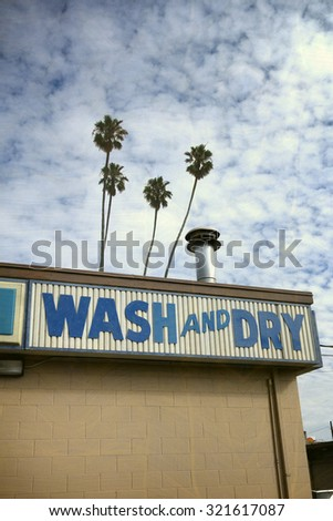 aged and worn vintage photo of laundromat sign with palm trees                                - stock photo