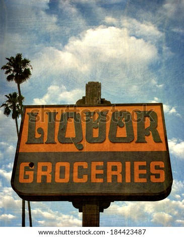 aged and worn vintage photo of liquor and groceries sign with palm trees                                - stock photo