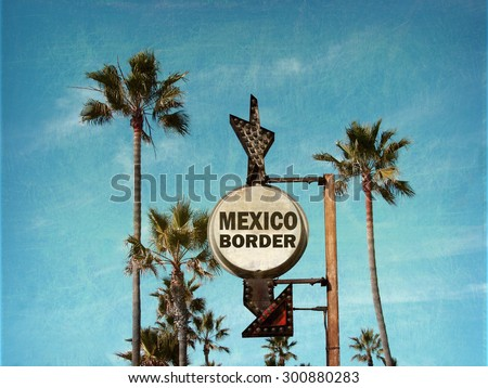 aged and worn vintage photo of mexico border sign with palm trees                              - stock photo