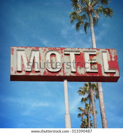 aged and worn vintage photo of neon motel sign with palm trees                              - stock photo