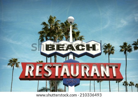 aged and worn vintage photo of neon sign on beach with palm trees                               - stock photo