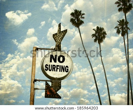 aged and worn vintage photo of no surfing sign on beach with palm trees - stock photo