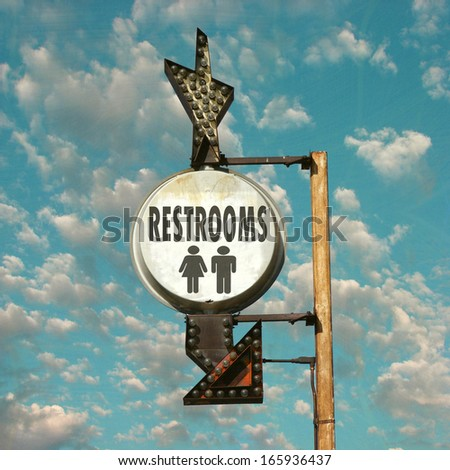 aged and worn vintage photo of restroom sign with arrow - stock photo