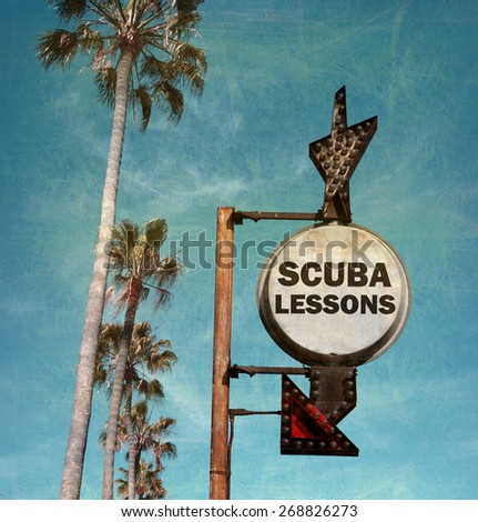 aged and worn vintage photo of scuba lessons sign with palm trees - stock photo