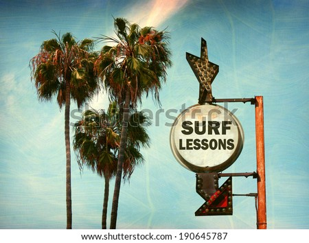 aged and worn vintage photo of surf lessons sign on beach with palm trees - stock photo