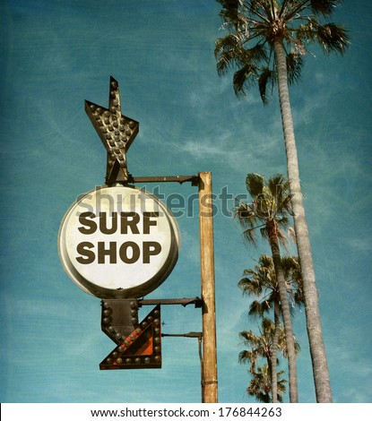 aged and worn vintage photo of surf shop sign on beach with palm trees - stock photo