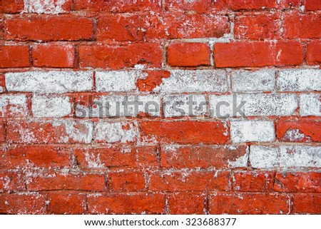 Aged architecture detail. Grunge brick wall half painted in red color. Half-painted weathered brick wall with a lot of copy space - stock photo