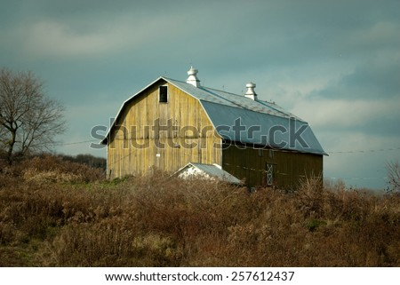 Aged Barn Along the NY State Country Side is a landscape photograph of a yellowish barn found on the country roads of New York State against a stormy bluish gray sky. - stock photo
