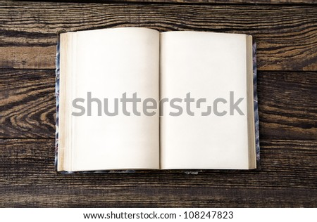 Aged blank book on wooden table, blank pages - stock photo