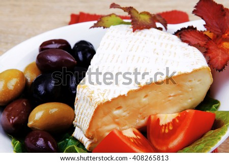 aged brie cheese on salad in white dish over red cloth on with olives and tomato over wooden table - stock photo
