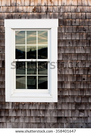 Aged cedar shingles with a white window - stock photo