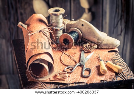 Aged cobbler workplace with tools, shoes and laces - stock photo