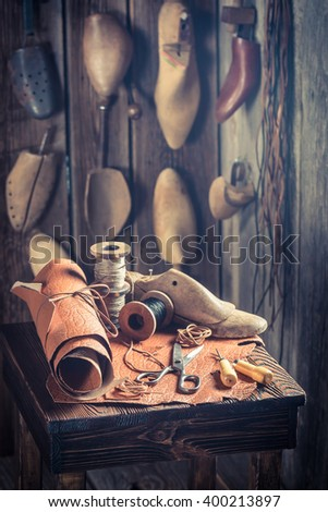 Aged cobbler workplace with tools, shoes and leather - stock photo