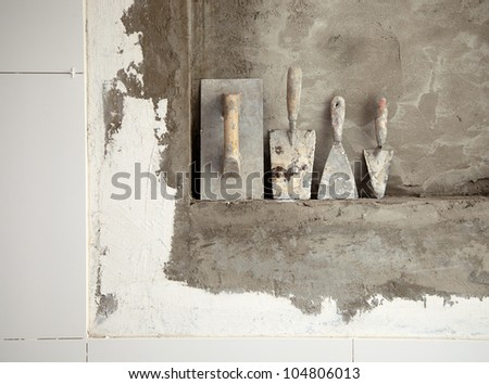 aged construction cement used tools grunge on mortar wall - stock photo