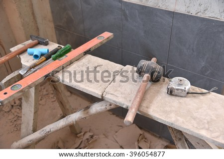 aged construction cement used tools grunge on tile wall - stock photo