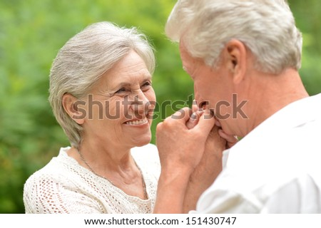 Aged couple enjoying each other in green summer park - stock photo