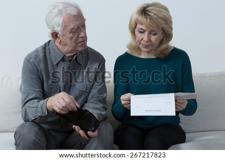 Aged couple sitting on the sofa and analyzing unpaid bills - stock photo