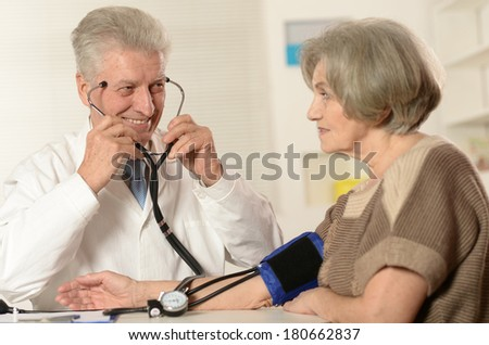 Aged doctor with a elderly patient in his office measuring pressure - stock photo