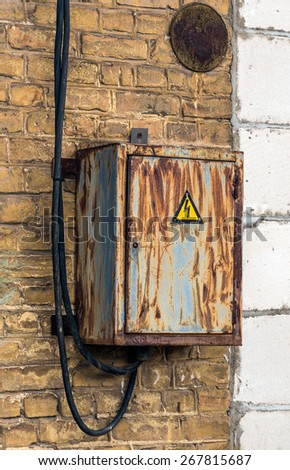 Aged electric switch box in front of old brick wall background - stock photo