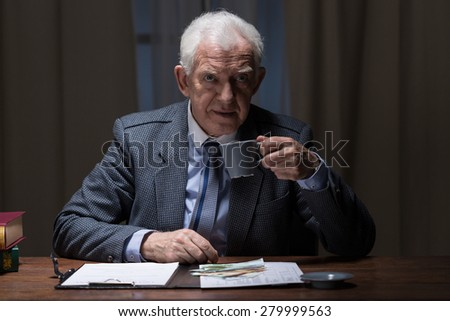Aged elegant working man sipping hot coffee in the evening - stock photo