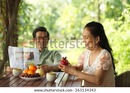 Aged family breakfast: woman peeling an apple while her husband reading a newspaper - stock photo