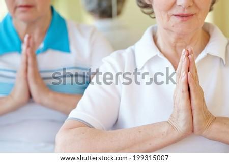 Aged female doing yoga exercise for balance - stock photo
