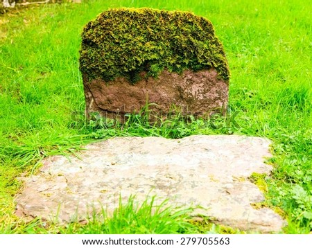 Aged gravestone tombstone with moss green grass in an ancient church graveyard - stock photo