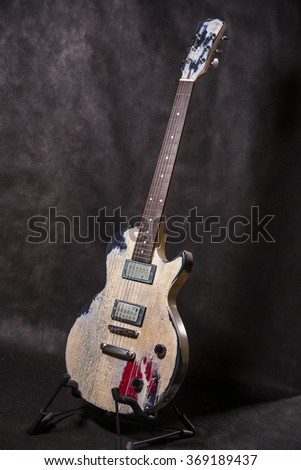 Aged guitar front on black background - stock photo
