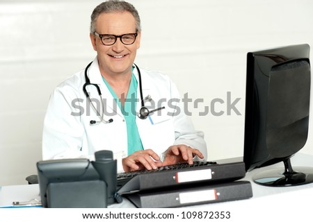 Aged male doctor in glasses working on computer, smiling at camera - stock photo
