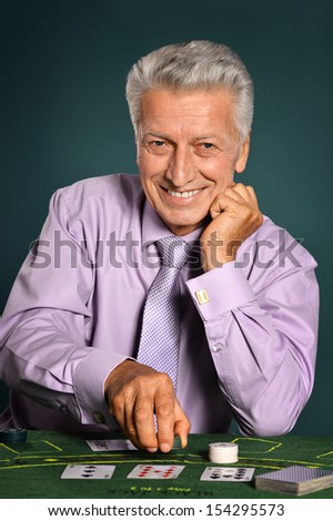 Aged man playing in casino - stock photo