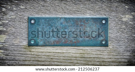 Aged metal plate on wooden background - stock photo