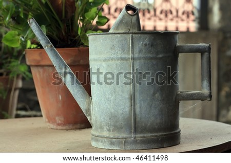 Aged metallic watering can on the garden table - stock photo