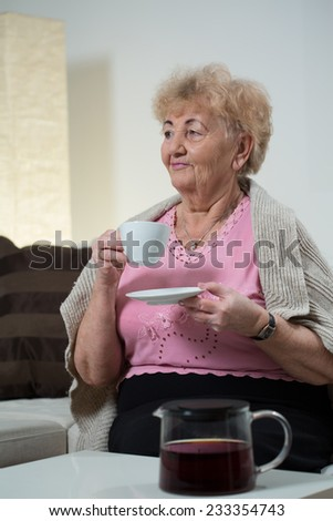 Aged nice lady drinking cup of black coffee - stock photo