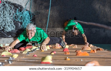 Aged Person Doing Extreme Sport Elderly Female Moving Up on Outdoor Climbing Wall Sporty Clothing on Fitness Training Intense but Positive Face another Climber Start His Ascent on Background - stock photo