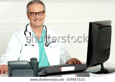 Aged physician with stethoscope around his neck looking at camera - stock photo