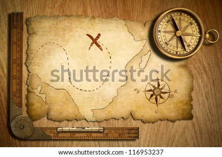 aged treasure map, ruler and old brass compass on wooden table top view - stock photo